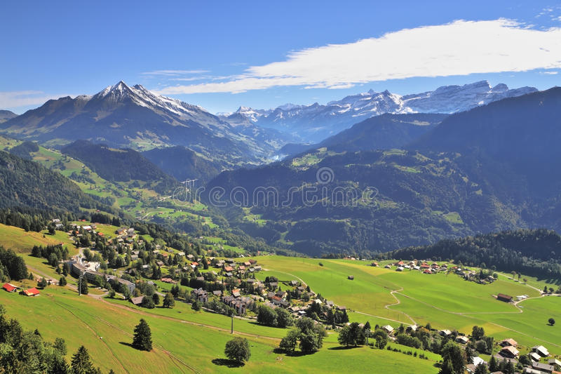 Gorgeous weather in the resort of Leysin. Gorgeous weather in the resort town of Leysin in the Swiss Alps. Picturesque gentle alpine meadows and rural houses royalty free stock photo