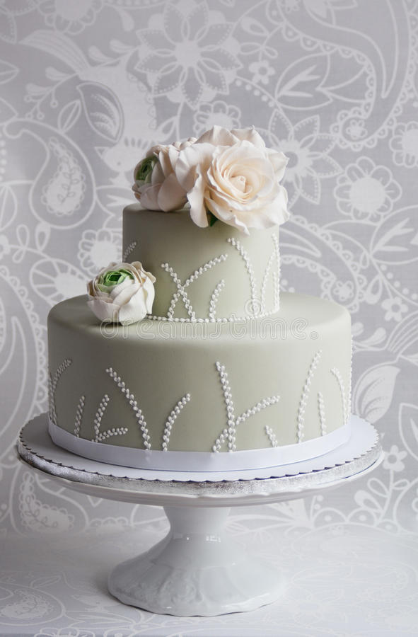Gorgeous wedding cake. Covered with grey fondant and decorated with white gum paste rose and ranunculuses stock photography