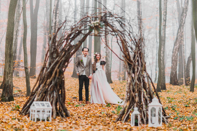 Gorgeous wedding couple under the mysterious hazel arch decorated with decorations in autumn woods stock photos