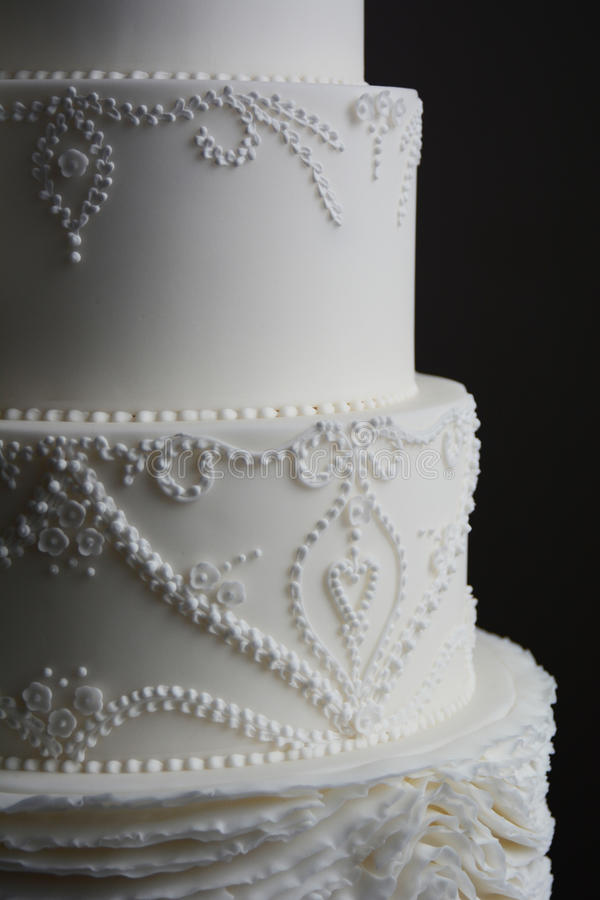 Gorgeous white wedding cake. Decorated with gum paste flowers and royal icing stock image