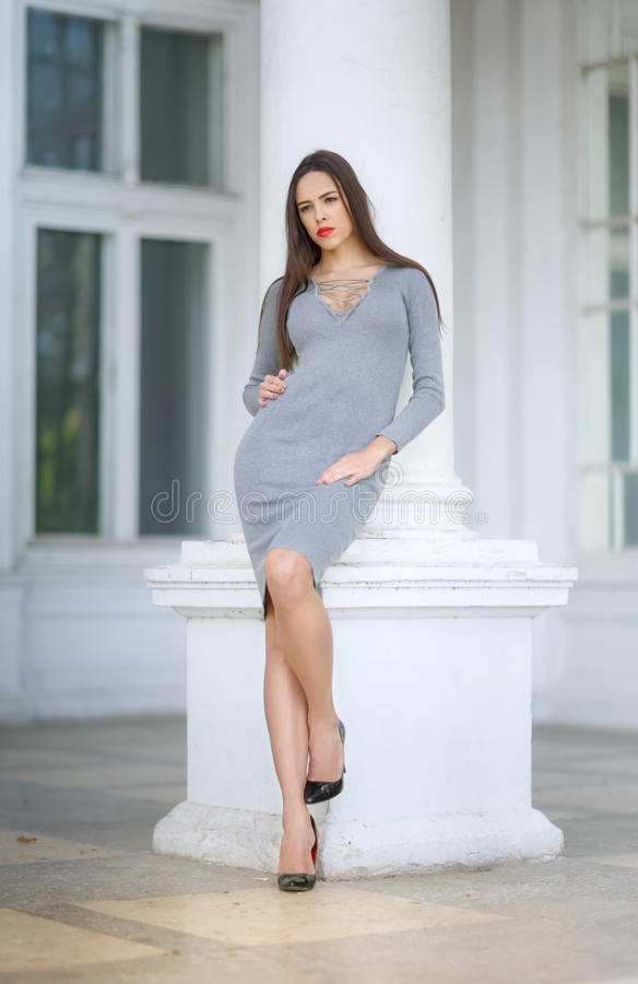 A gorgeous woman on the background of great white column. The beautiful lady in a gray dress and black shoes outdoors. stock photos