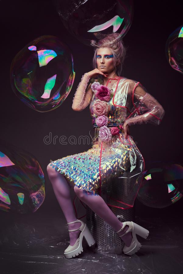 Female in fashion transparent raincoat with splendid make up and hairstyle royalty free stock images