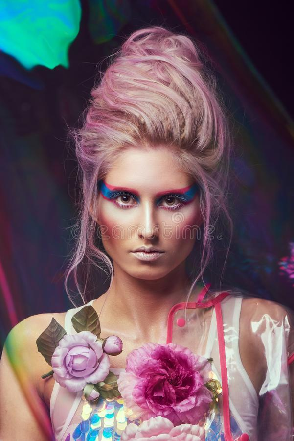 Female in fashion transparent raincoat with splendid make up and hairstyle stock photography