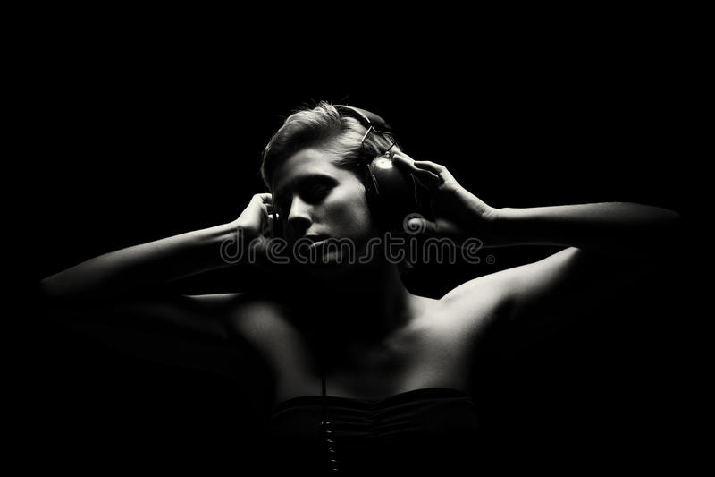 Gorgeous woman in black and white listening to music stock photography