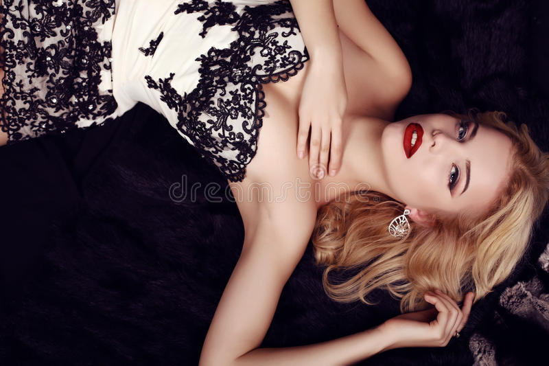 Gorgeous woman with blond hair wears luxurious party dress and bijou. Fashion studio photo of gorgeous sensual woman with blond hair and evening makeup,wears royalty free stock image