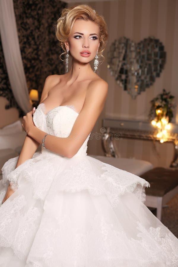 Gorgeous woman with blond hair wears luxurious wedding dress and bijou. Fashion studio photo of gorgeous bride with blond hair, in luxurious wedding dress with stock photos