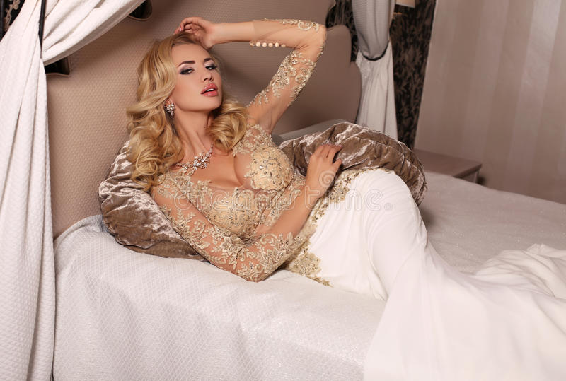 Gorgeous woman with blond hair wears luxurious wedding dress and bijou. Fashion studio photo of gorgeous bride with blond hair, in luxurious wedding dress with stock images