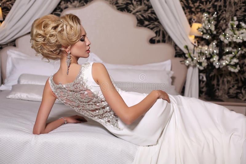 Gorgeous woman with blond hair wears luxurious wedding dress and bijou. Fashion studio photo of gorgeous bride with blond hair, in luxurious wedding dress with royalty free stock photos