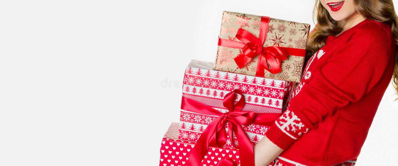 Gorgeous woman in christmas jumper holding loads of heavy xmas presents, christmas banner, isolated royalty free stock images