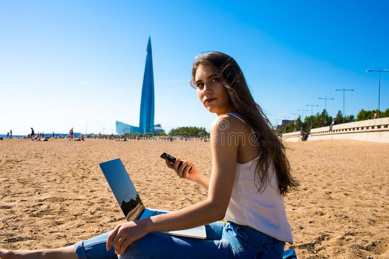 Gorgeous woman copywriter waiting call on mobile phone during distance work on laptop computer thoughtful looking away royalty free stock images
