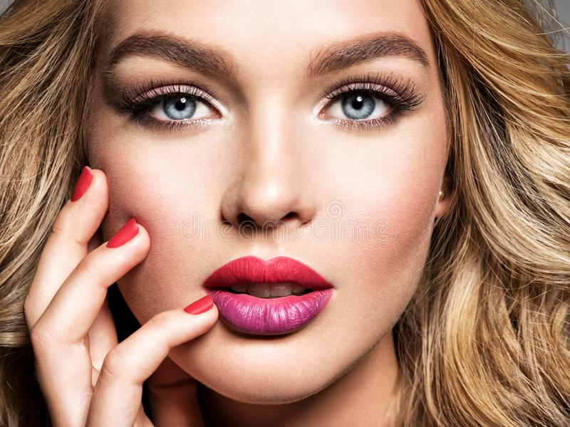 Gorgeous woman with  curly beautiful hair. Makeup. Bright colored lips royalty free stock images