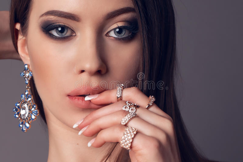 Gorgeous woman with dark hair and bright makeup with luxurious bijou stock images