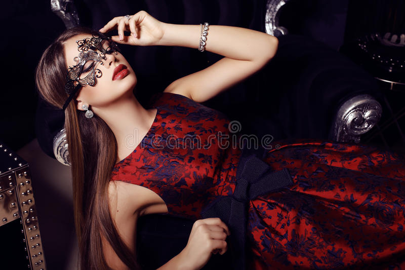 Gorgeous woman with dark hair in elegant dress and mask stock images