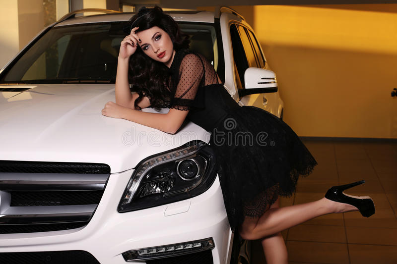 Gorgeous woman with dark hair wears luxurious dress,posing beside white car. Fashion photo of gorgeous woman with dark hair wears luxurious dress,posing beside stock photography