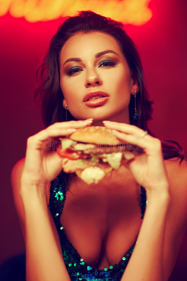 Gorgeous woman eating hamburger in night club royalty free stock photography
