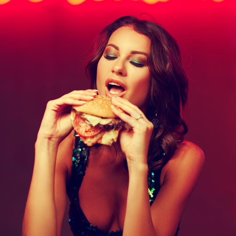Gorgeous woman eating hamburger in night club stock images