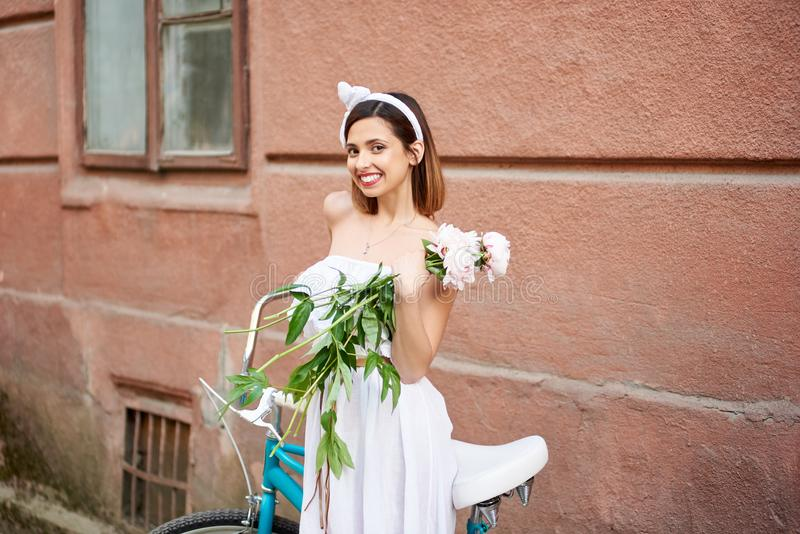 Gorgeous woman holding flowers posing near her bicycle royalty free stock photo