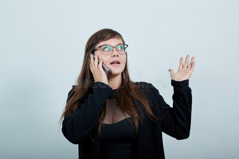 Gorgeous woman holding IPhone, talking about something. Gorgeous caucasian young woman on pretty clothes holding IPhone, talking about something over isolated royalty free stock image