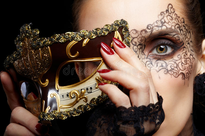 Gorgeous woman in mask. Close-up portrait of beautiful brunette woman with facial body art hiding half of her face with carnival venetian mask stock photography