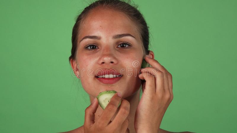 Gorgeous woman massaging her face with slices of cucumber royalty free stock photo