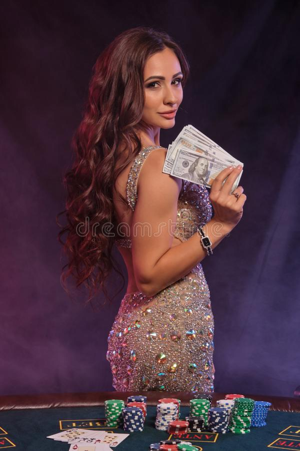 Girl playing poker, casino. Holding cash, posing at table with stacks of chips, money, cards. Black, smoke background royalty free stock photography