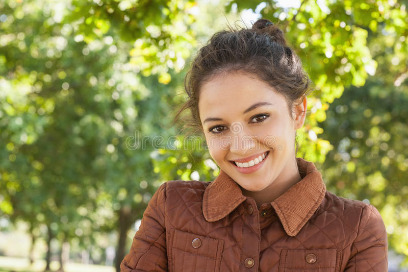 Gorgeous woman posing wearing a coat in a park stock image