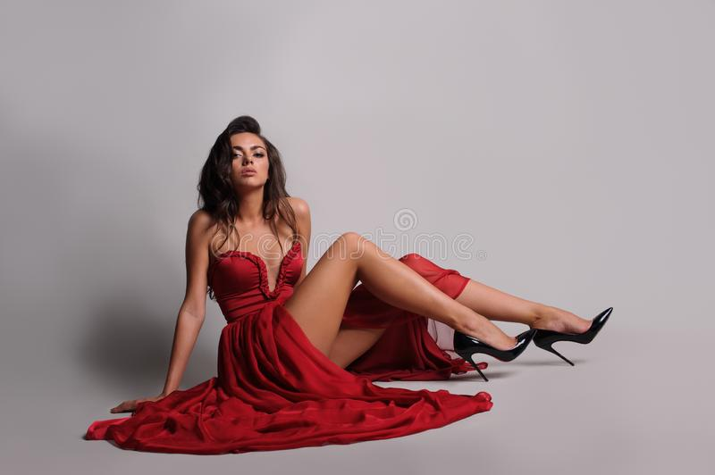 gorgeous woman in red dress. Studio picture, grey background stock image