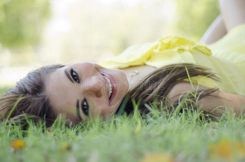 Gorgeous woman relaxing at the park. Cute young woman laying on the grass and smiling royalty free stock images