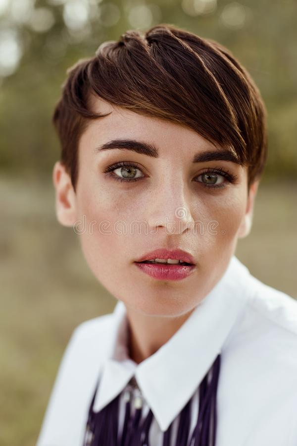 Gorgeous woman with short hair posing outdoors royalty free stock photography