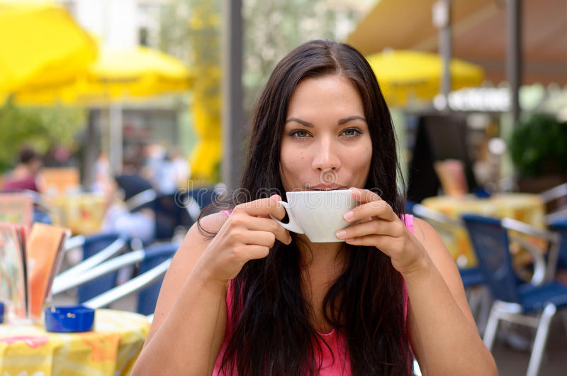 Gorgeous woman sipping coffee. In cafe with out of focus yellow umbrellas and tables in background with copy space stock photography