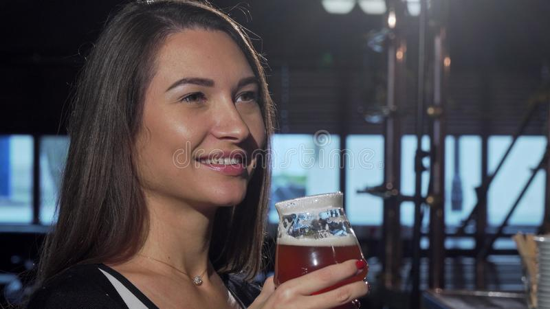 Gorgeous woman smelling and drinking delicious beer at the pub royalty free stock photo