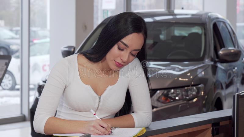 Gorgeous woman smiling to the camera, signing papers after buying new car royalty free stock photography