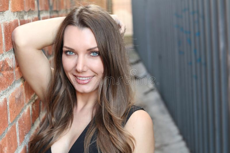 Gorgeous woman smiling on urban background royalty free stock photography