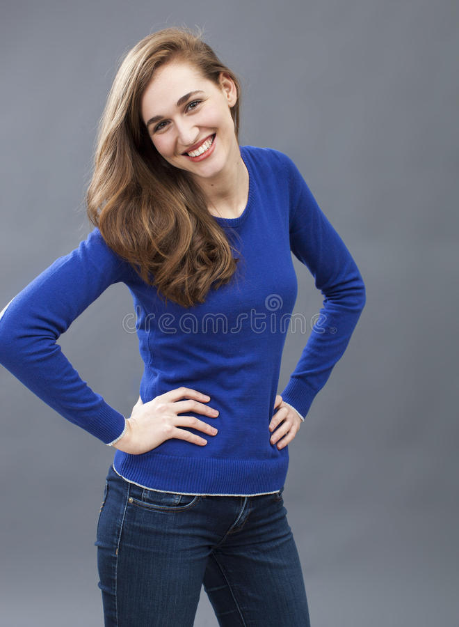 Gorgeous woman standing with natural seductive body language. Seduction concept - portrait of smiling beautiful girl standing with both hands to her waist for stock image