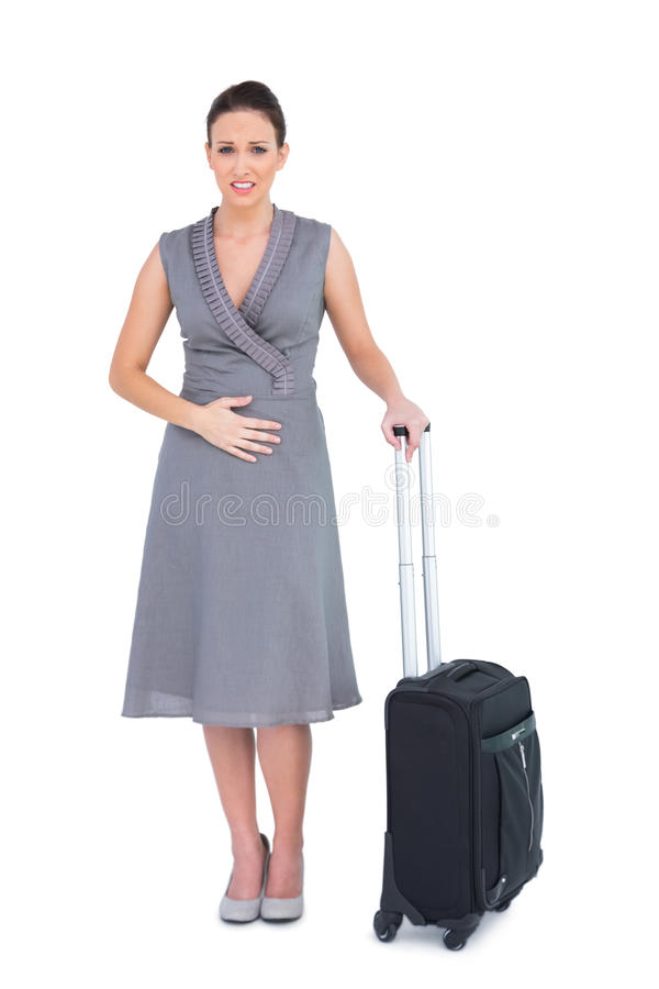 Gorgeous woman with suitcase having stomach ache stock photos