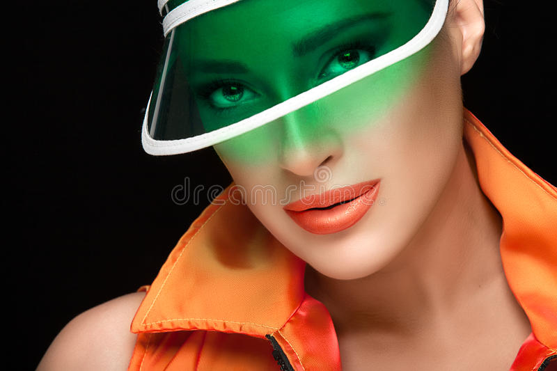 Gorgeous Woman in Sun Visor Looking at Camera. Sports fashion portrait. Close up Gorgeous Woman Face in Green Transparent Plastic Sun Visor and Orange Collared royalty free stock images