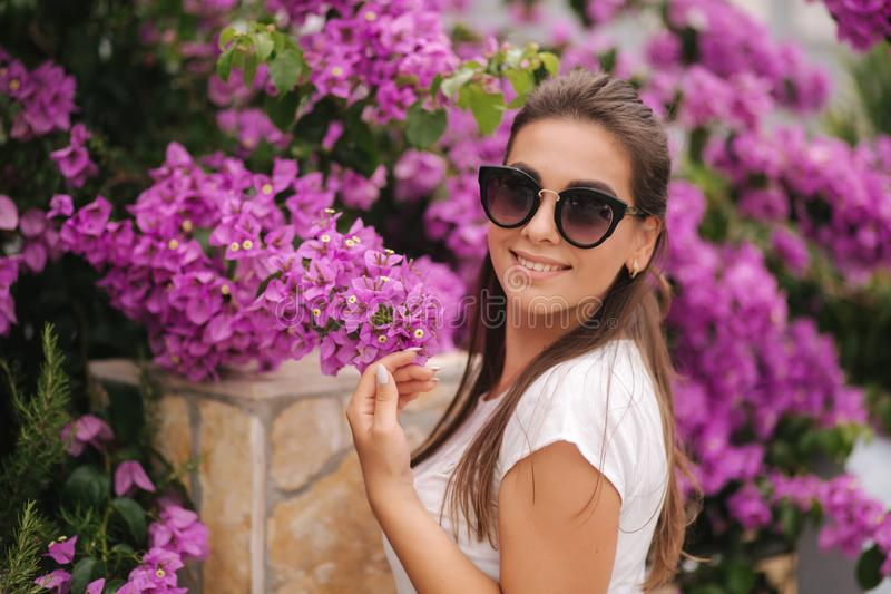 Gorgeous woman in sunglasses stand in beautiful flowers. Portrait of happy smiled young woman stock image