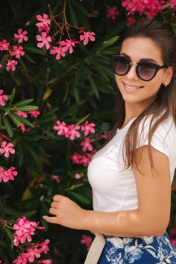 Gorgeous woman in sunglasses stand in beautiful flowers. Portrait of happy smiled young woman stock photography