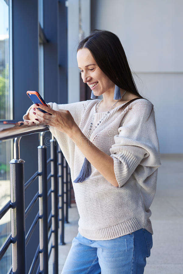 Gorgeous woman surfing in phone while leaning on handrail. Vertical of gorgeous woman surfing in phone while leaning on handrail stock photos