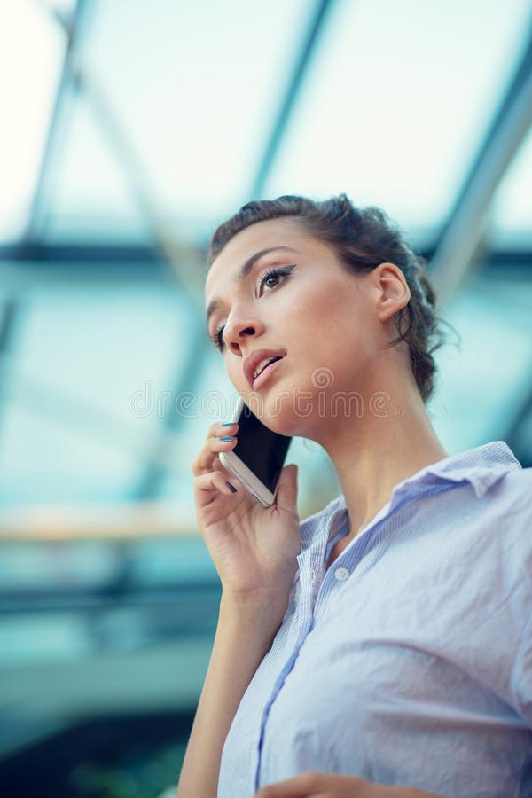 Gorgeous woman talking on mobile phone at airport royalty free stock photography