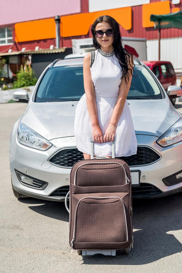 Gorgeous woman traveler with suitcase and car royalty free stock photos