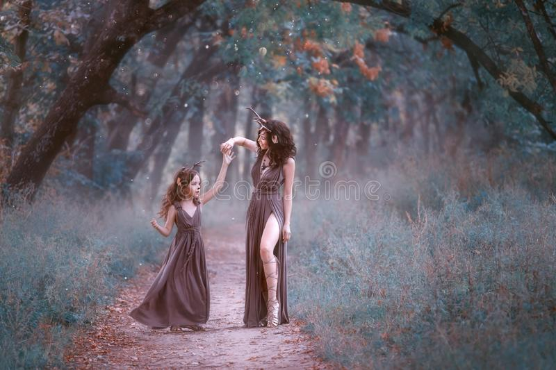 Gorgeous woman in deer costume is spinning her daughter on a forest trail, wearing long brown dresses, showing her royalty free stock image