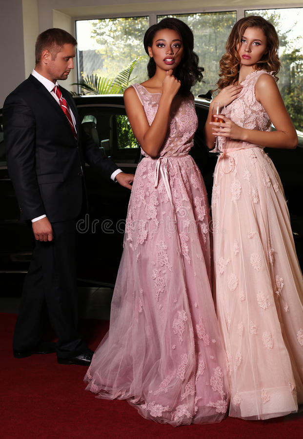 Gorgeous women wear luxurious dress,posing on red carpet. Fashion photo of gorgeous women with long dark hair wear luxurious dresses and men in elegant costume royalty free stock image