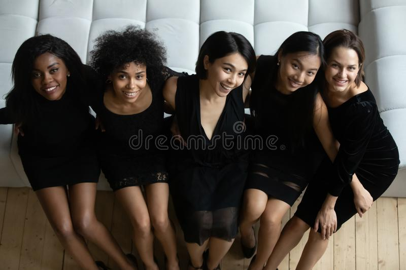 Gorgeous women wearing dresses sit on sofa looking at camera royalty free stock photo