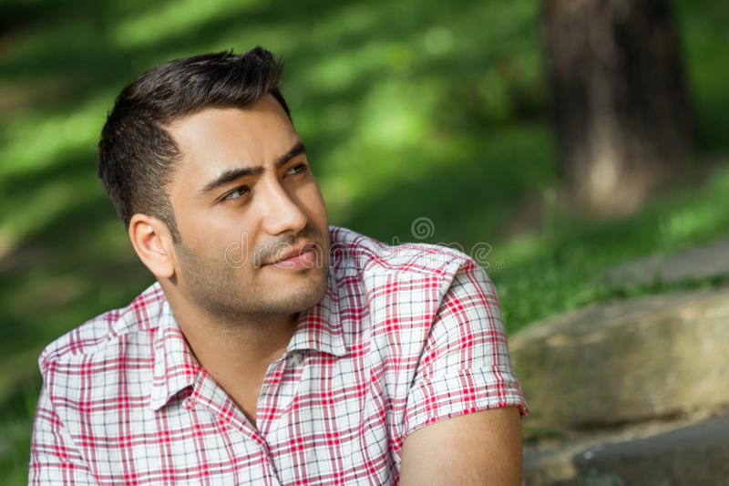 Gorgeous young attracive man in nature. Portrait of a handsome guy stock photo
