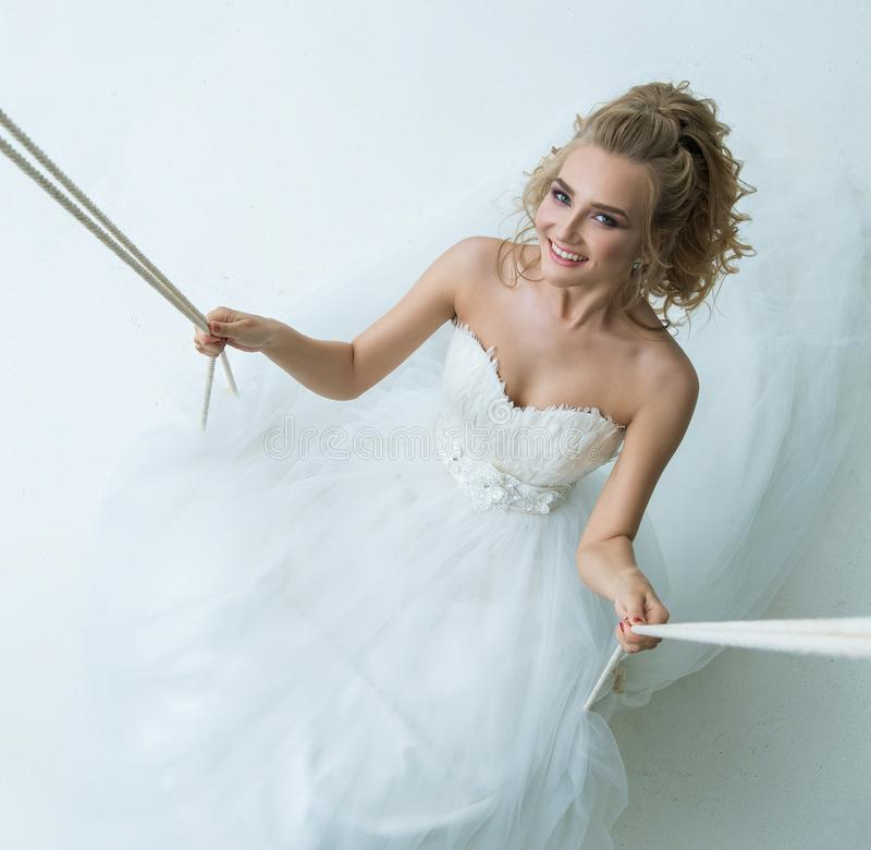 Gorgeous young bride on swing in studio royalty free stock photography