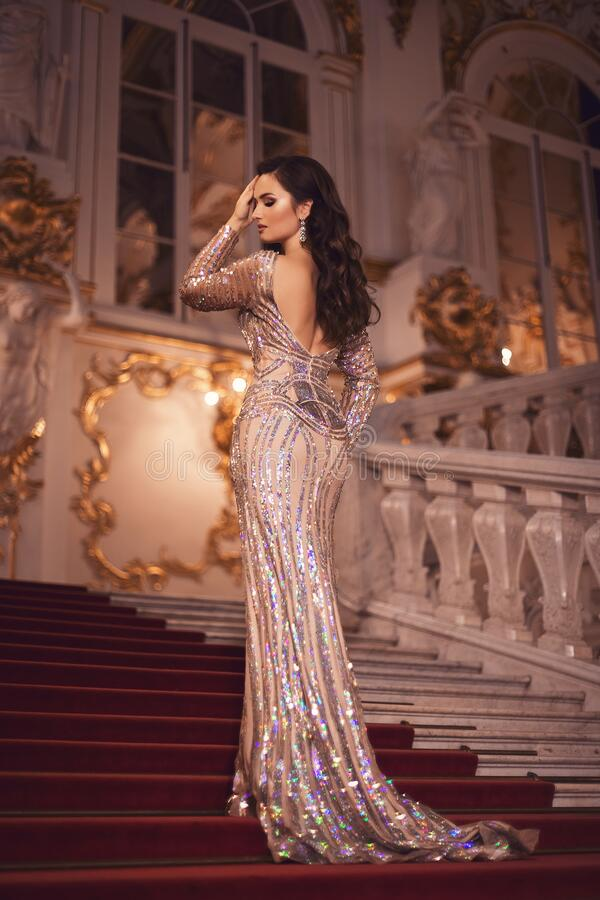 Gorgeous young brunette girl in a shiny ivory-sequined dress with an open back. Portrait of a gorgeous young brunette girl in a shiny ivory-sequined dress with stock image