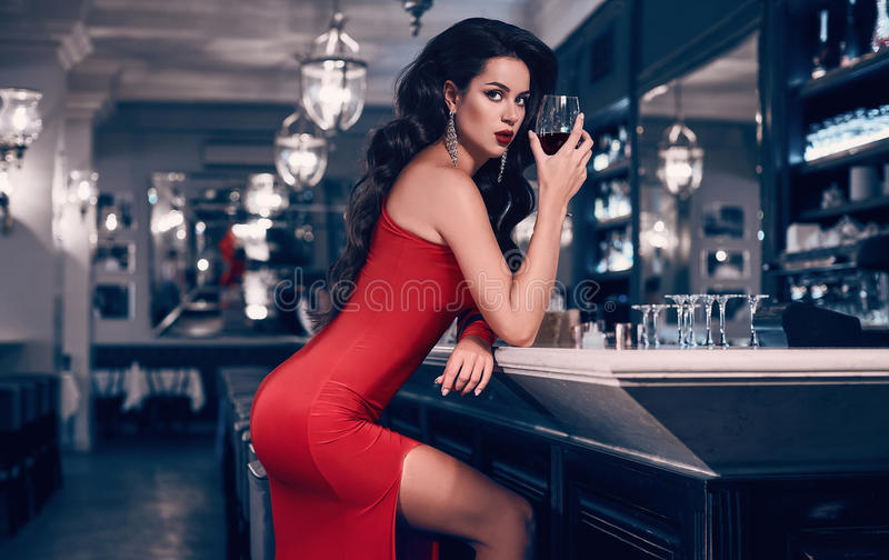 Gorgeous young brunette woman in red dress with wine. Gorgeous beauty young brunette woman in red dress with glass of wine standing at the bar in luxury interior royalty free stock image