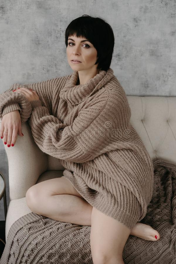 Gorgeous young brunette woman in warm knitted sweater posing stock image