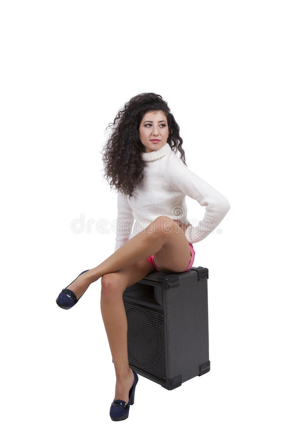 Gorgeous young female sitting on a audio speaker royalty free stock image